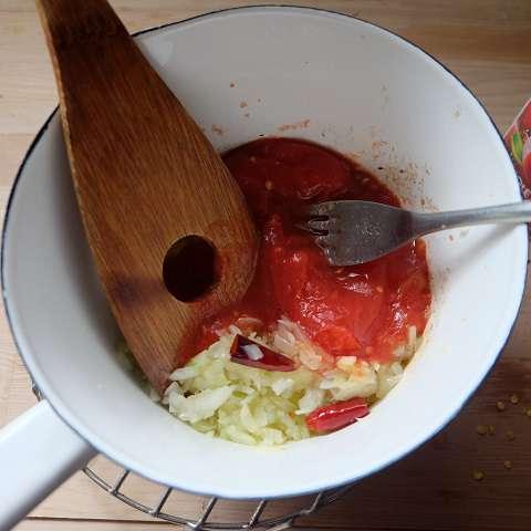 トマトをフォークで潰しながら入れ、半量になるくらいまで煮込む