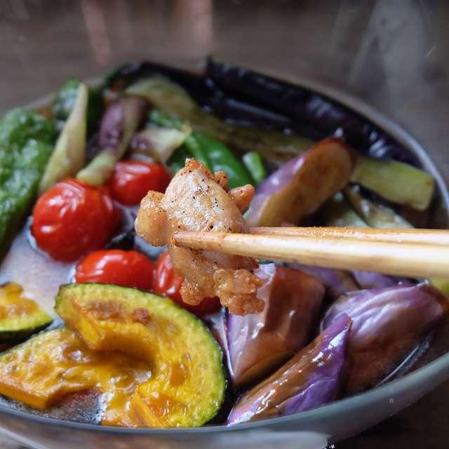 野菜と鶏肉をつゆに浸しているところの写真
