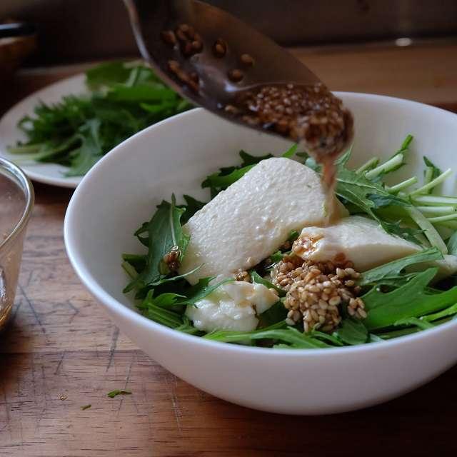 水菜に豆腐をスプーンですくって盛、ドレッシングをかけてるところ