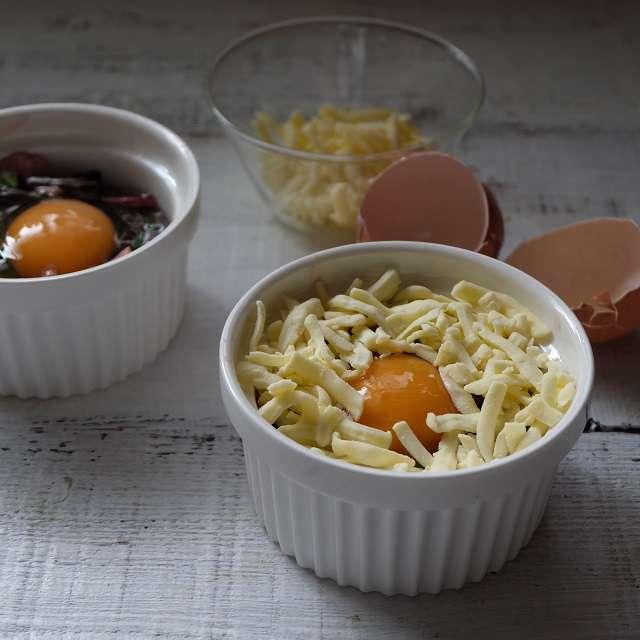 ほうれん草をココットに入れて卵を割り入れ、回りにチーズをおいているところ