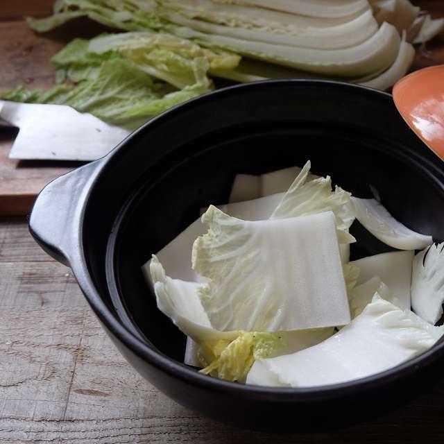 白菜の芯に近い葉の厚い部分を鍋に入れてるところ