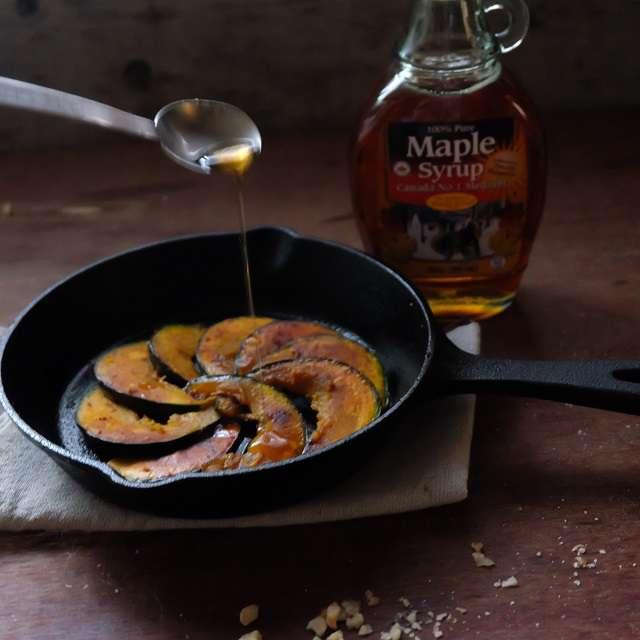 かぼちゃを裏返してスキレットに並べたら、メープルシロップをかけてるところ