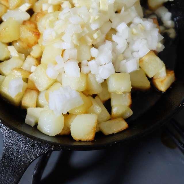 ジャガイモが色づいたら、玉ネギとニンニクを加え炒める