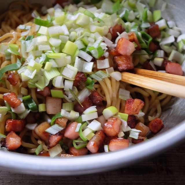 混ぜた調味料に茹でた麺と炒めたベーコンを入れ、さらに混ぜる