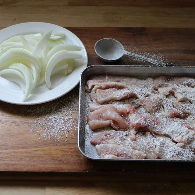 豚肉を切り、小麦粉を両面にふる、玉ネギはくし型に切る