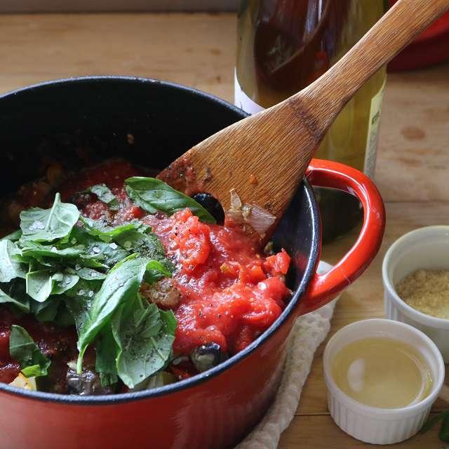 鍋に炒めたナスを戻し、ホールトマトを潰し、バジルの葉をちぎり入れ、残りの材料を加え45〜60分煮込む