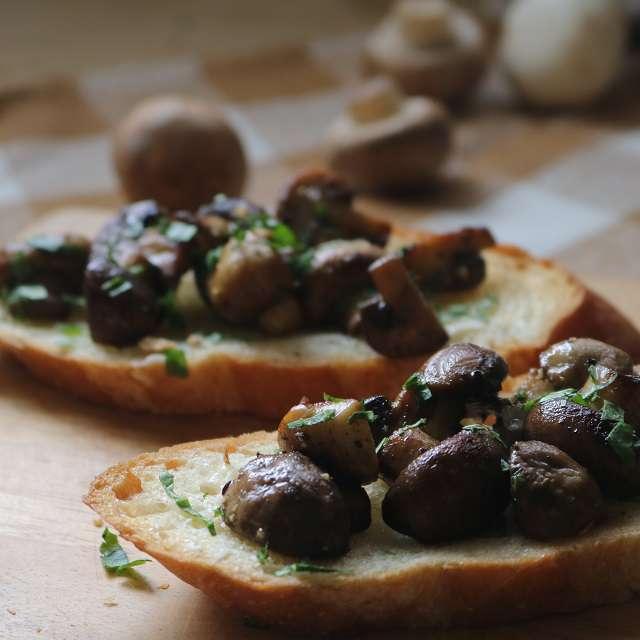 パンにマッシュルームをのせ、イタリアンパセリとおろしたパルミジャーノを降る