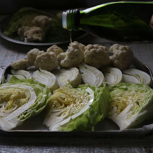 クッキングシートに切った野菜を並べ、オリーブオイルを回しかける