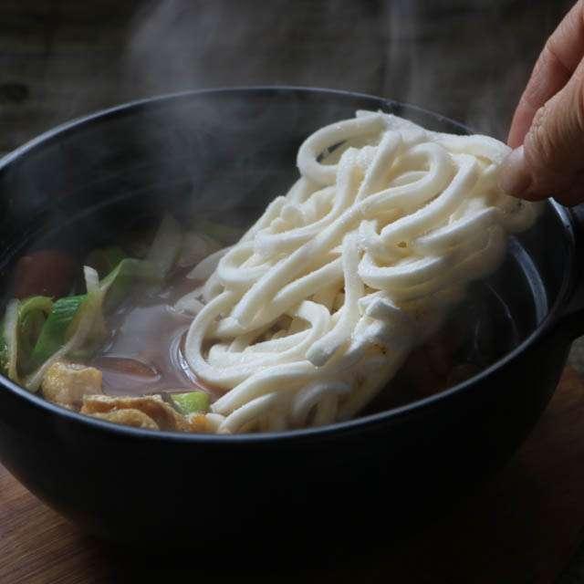 味噌と長ネギ、油揚げ、干し椎茸を入れ少し火を通し、冷凍うどんを加える
