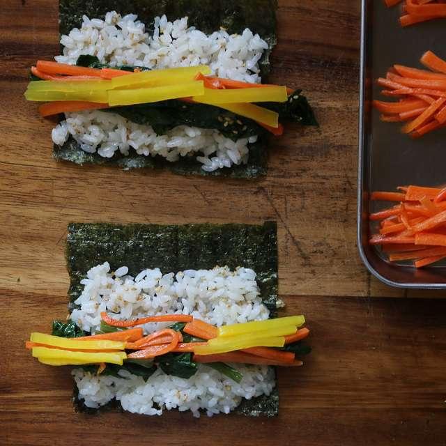 4等分に切った海苔をまな板にのせ、その上にご飯をのせて広げ、両端から中央へ具をのせる