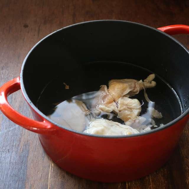 薄切りの生姜、鶏皮を入れ、沸騰したらアクを取り、弱火で5分煮る