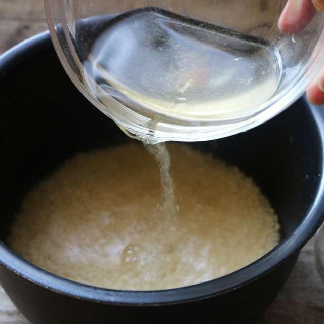 米を炊飯器に入れ、調味料を加え、ダシ汁を米2カップの目盛りまで加える