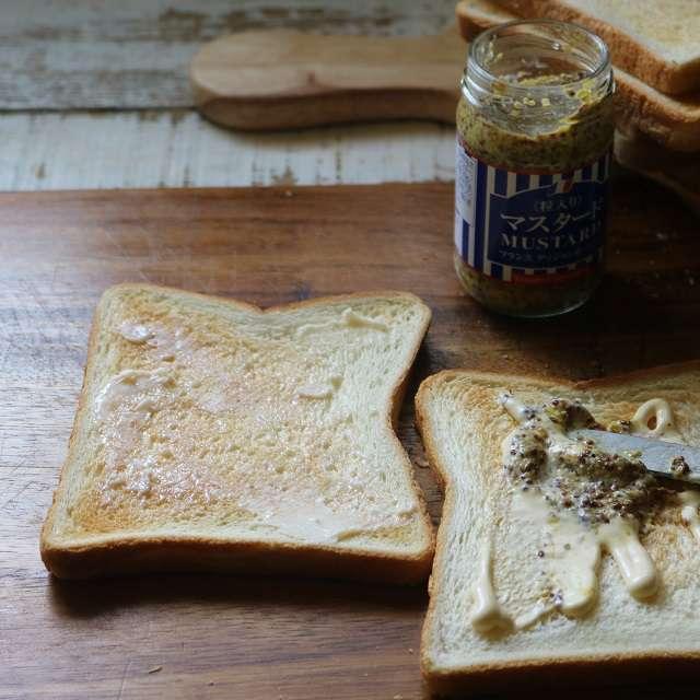 パンをトーストし、半分にバター、残りの半分にマヨネーズと粒マスタードを塗る