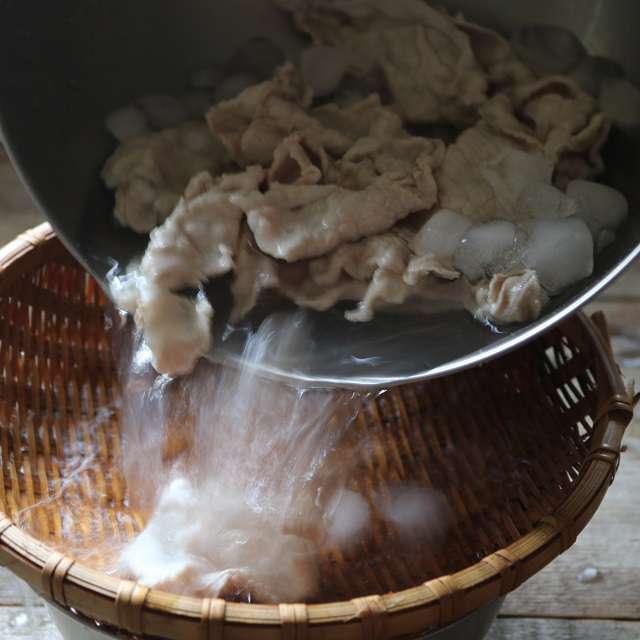 豚肉を冷水に取り、ザルに上げる