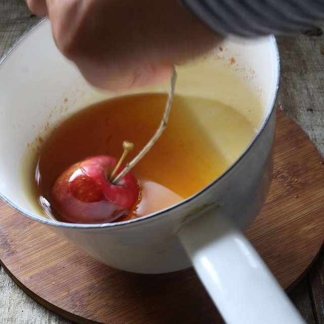 鍋を斜めにし、串にさしたりんごを飴に浸ける