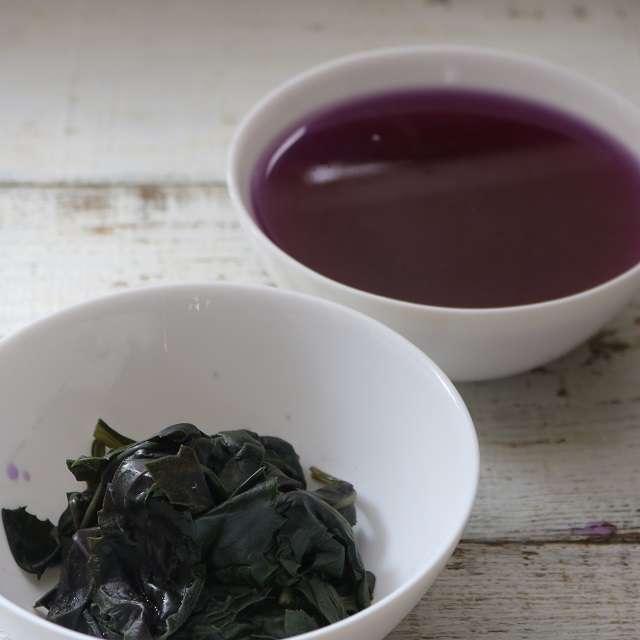 茹でた葉をザルにあげ、煮汁と葉に分け、葉を水分を絞る