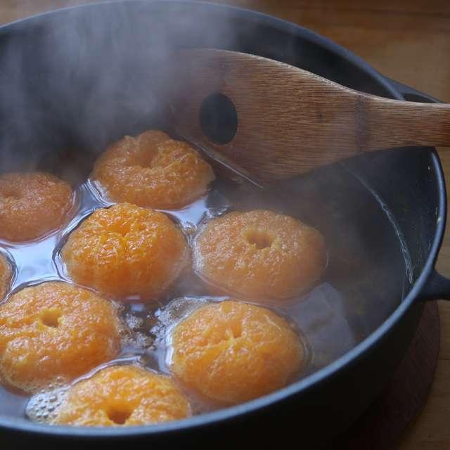 鍋に水と重曹を入れ火にかけ、泡が沸々と泡立つ状態で皮をむいたみかんを入れ、ひっくり返しながら90秒煮る