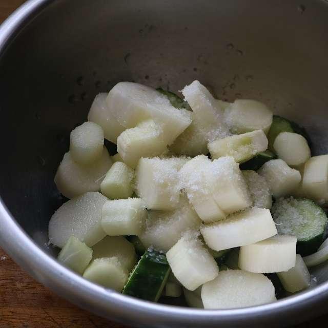 うどの水を切り、キュウリ、玉ネギと一緒にボウルに移し、野菜の2%の塩をまぶして30分ほど重石をする