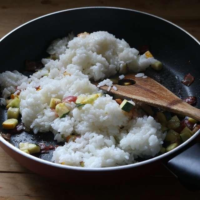 フライパンにご飯を加え、広げてほぐすを繰り返す。