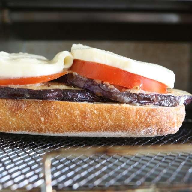 パンの上にナス、トマト、チーズの順にのせ、チーズがとろけるまでオーブントースターで焼く