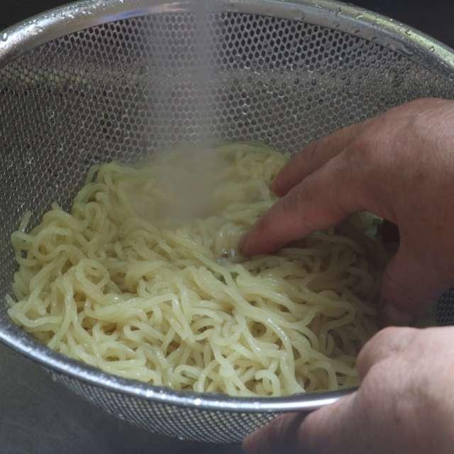 麺をパッケージの表示に従って茹で、流水で滑りがなかなるまで洗う