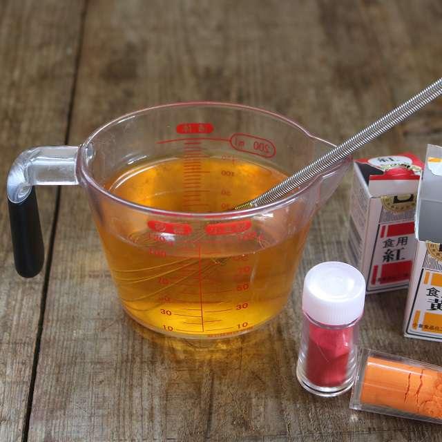 食用色素の黄色をぬるま湯に溶かし、紅色の少しずつ入れ柿色に調整して冷ます