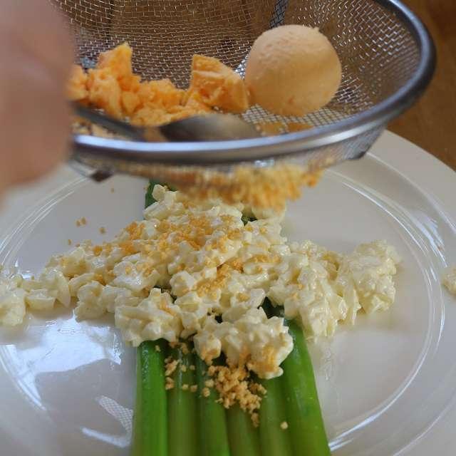アスパラガスを皿に置き、⑧をのせたら、黄身をザルや茶こしでこしながらかける