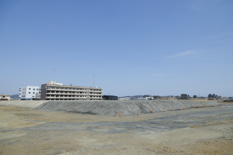 更地のなかに建つ伝承館と、震災遺構として残された宮城県気仙沼向洋高校の旧校舎