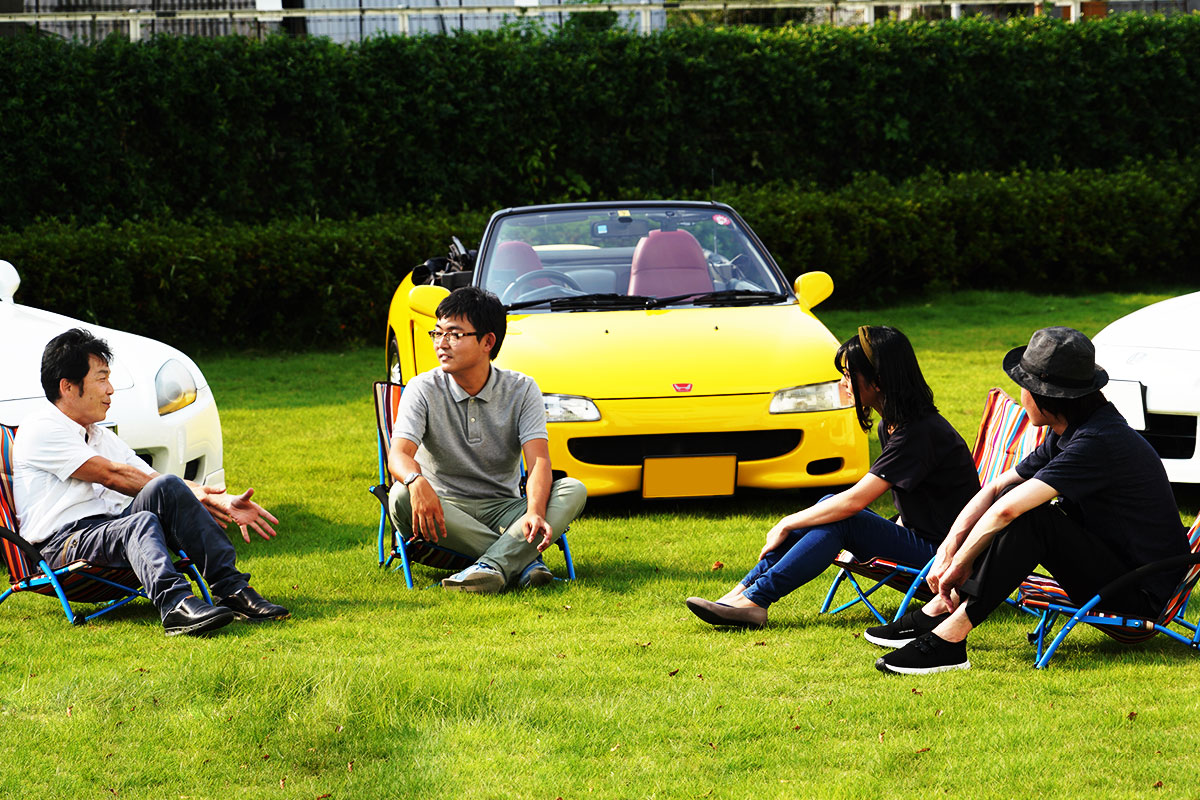 4人の座談会メンバーがオープンカーについて語り合っている風景