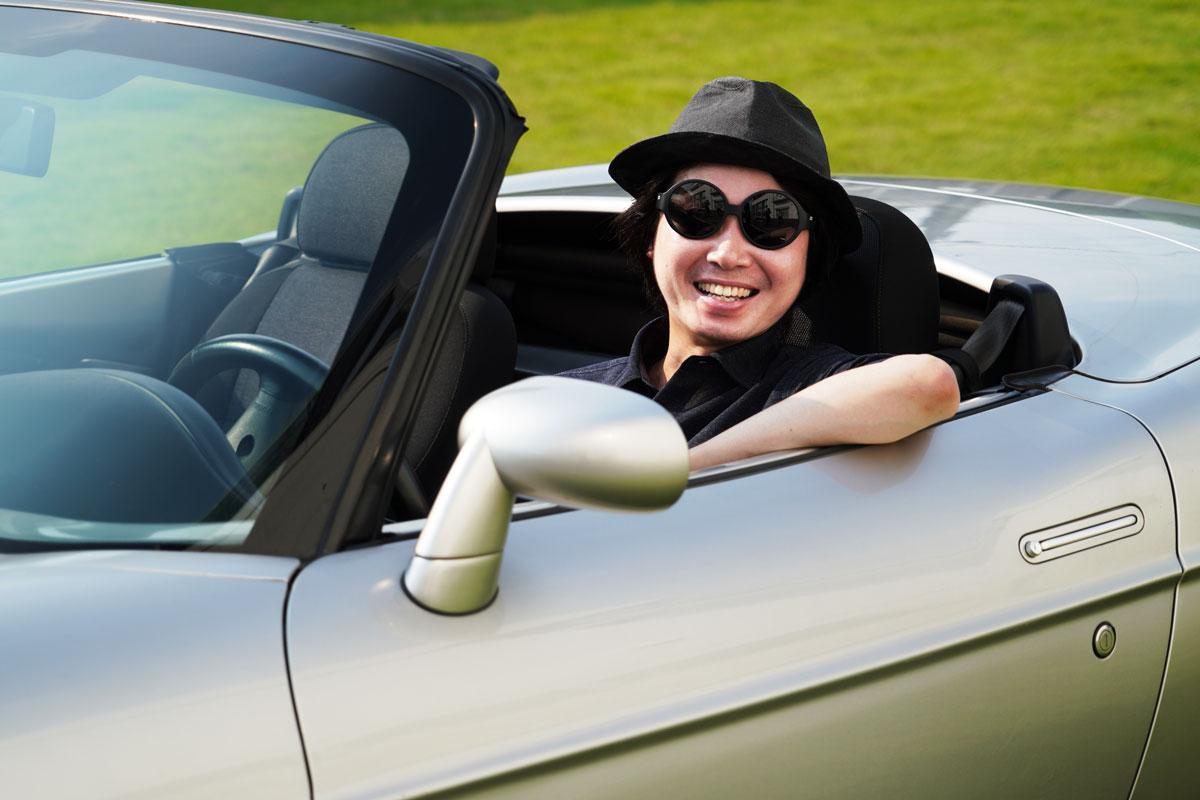 愛用のサングラスと帽子をつけて愛車FIAT「バルケッタ」に乗る佐藤さん