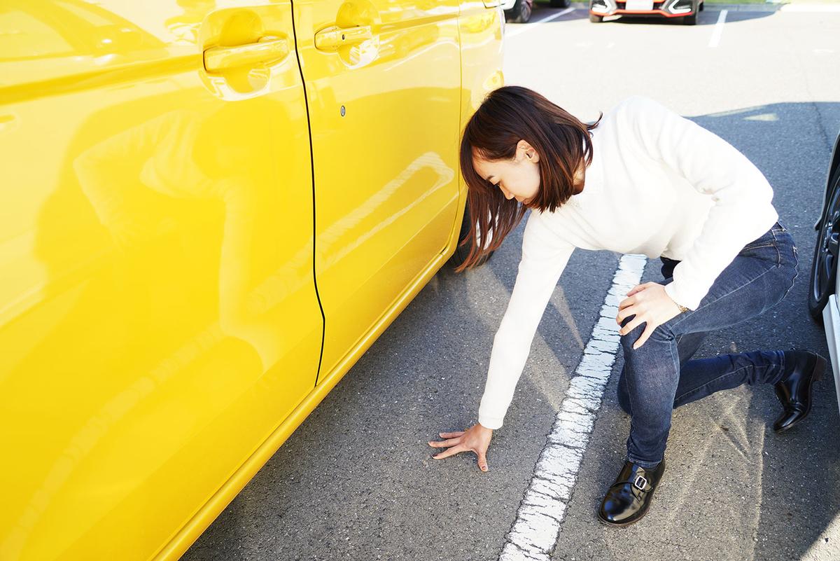 車に乗車するときに発生する静電気を防ぐために乗車前に地面に手を触れているようす