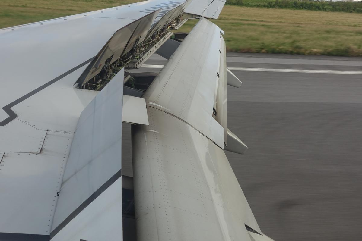 飛行機の翼についたスポイラーが立ち上がっているようす