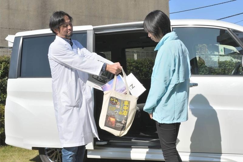 Car寝る博士が大量にクルマのカタログが入った肩掛けカバンを渡そうとしている写真