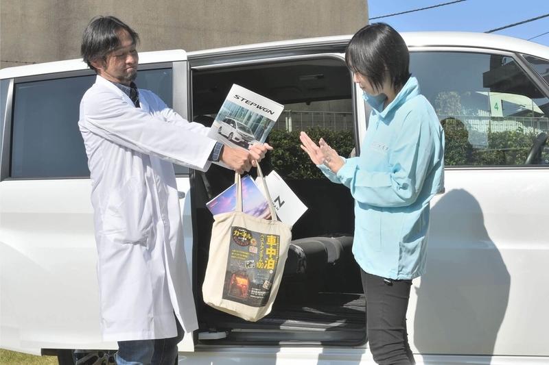 Car寝る博士が大量にクルマのカタログが入った肩掛けカバンを渡そうとして断られている写真