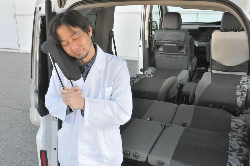 Car寝る博士がステップワゴンの近くに立ってヘッドレストに頬ずりしている写真