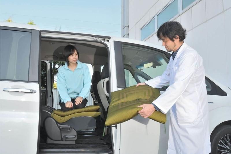 Car寝る博士がステップワゴン スパーダの車内に座るカエライフ編集部員に座布団をあげている写真