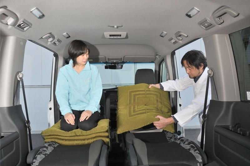 ステップワゴン スパーダの車内で座布団に正座しているカエライフ編集部員にCar寝る博士が座布団をあげている写真
