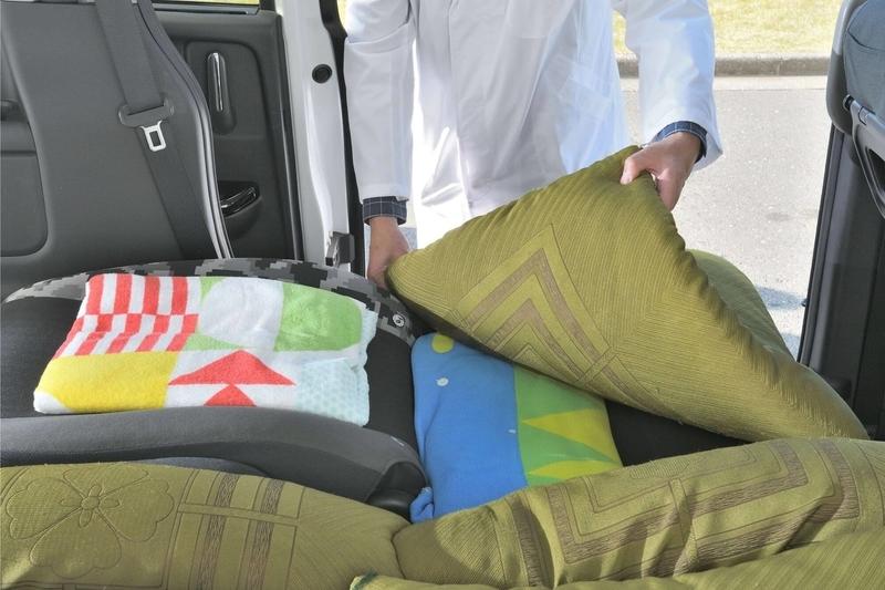 ステップワゴン スパーダの2列目を後ろに倒した状態で、シートに生まれる段差を薄手のブランケット、大きめのバスタオル、座布団などを使って段差を埋めている写真