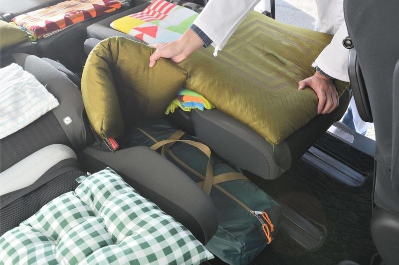 ステップワゴン スパーダの2列目のキャプテンシートの間にうまれる隙間をバックと座布団を使って埋めている写真