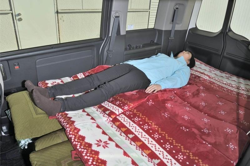 ステップワゴンスパーダの2列目3列目を倒し、車中泊用のシートアレンジにして、段差を埋めてフラットにしたところにお昼寝マットを敷いたところに身長163㎝の女性がひとり寝ている写真