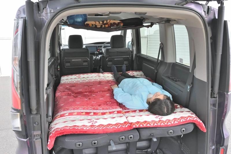2列目がベンチシートタイプのステップワゴンスパーダを車中泊仕様のシートアレンジにして、段差を埋めた上にお昼寝マットを敷いてフラットにして、その上に女性ひとりが寝ている写真