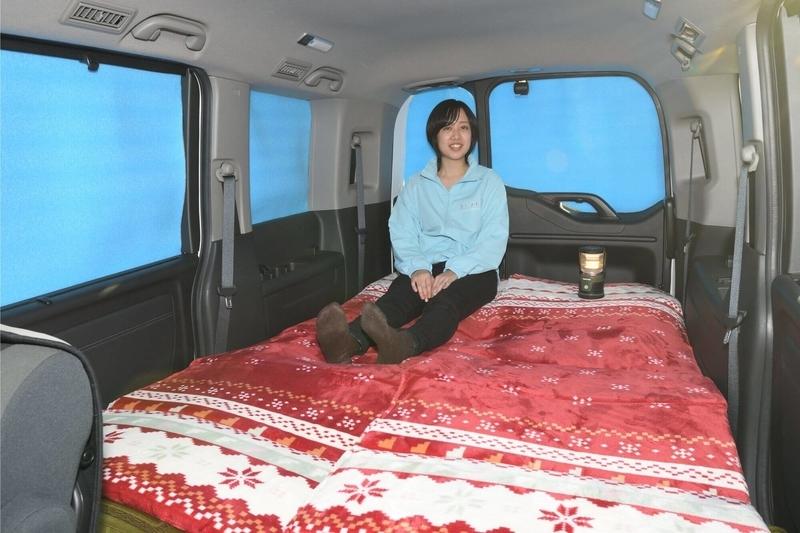 車中泊仕様にフラットにし、銀マットで目隠しシェードをしたステップワゴンの車内で女性がくつろいで座っている写真