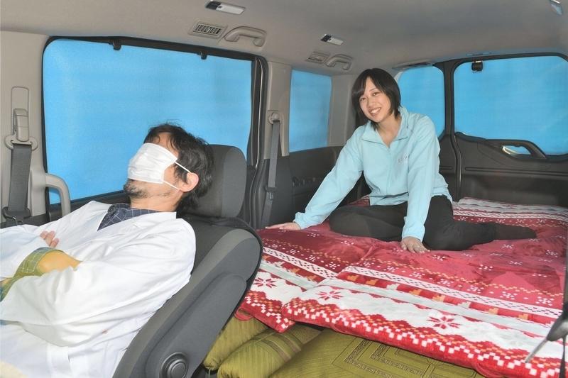 車中泊仕様にして目隠しシェードをしたステップワゴンスパーダの車内でひとりの女性が座って、運転席にCar寝る博士が座っている写真