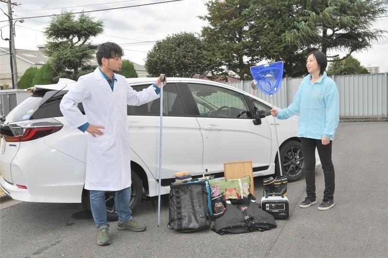 Honda シャトルの横に車中泊するための荷物を並べている写真
