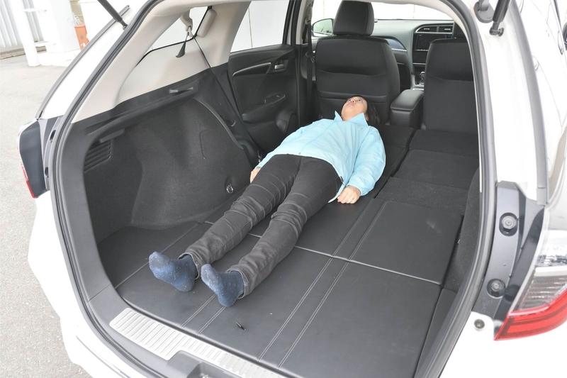 Hondaシャトルの後部座席をすべて倒し、荷室をフラットの車中泊仕様にしたところに身長163cmの女性がひとり寝ている写真