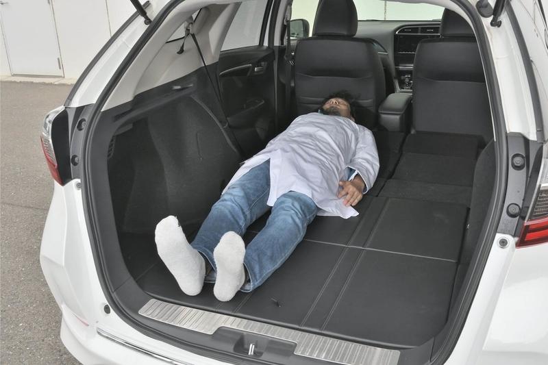Hondaシャトルの後部座席をすべて倒し、荷室をフラットの車中泊仕様にしたところに身長175cmの男性がひとり寝ている写真