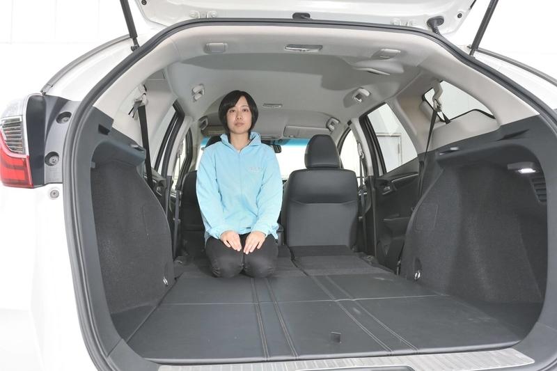 Honda シャトルの後部座席をすべて倒し荷室を車中泊仕様のフラットにしたところに女性がひとり正座している写真