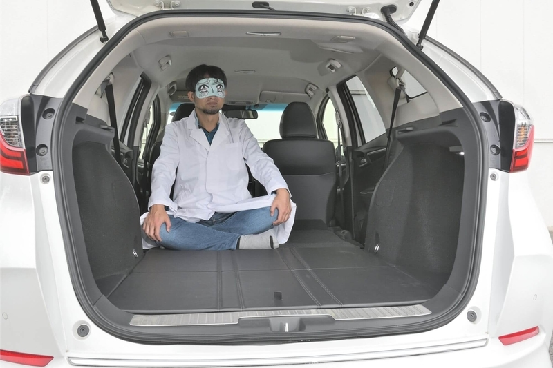Honda シャトルの後部座席をすべて倒し荷室を車中泊仕様のフラットにしたところに男性がひとりあぐらをかいている写真