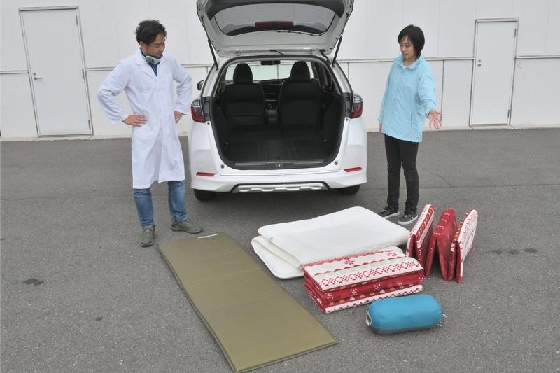 Hondaシャトルの荷室の前で、ニトリの布団やお昼寝マット、キャンプ用のエアマットなどを並べてCar寝る博士とカエライフ編集部が見ている写真