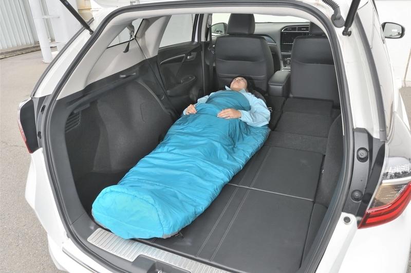 車中泊仕様にフラットにしたHondaシャトルの荷室で女性が寝袋に入って寝ている写真